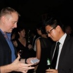 Shaun setting his card magic trick up with a guests at a cocktail function about to be awed.