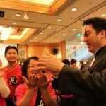 magician performing roving card magic to runner at the Li & Fung Standard Chartered Hong Kong Marathon after party in Regal Hotel