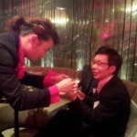 Roving magician performing coins trick  to CEO at DBS Hong Kong cocktails event
