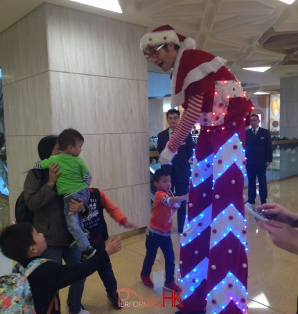Led stilt performer shaking hands with young child in a shopping mall in Hong Kong