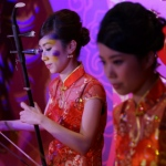 Erhu musicians performing lively Chinese music at a dinner event.
