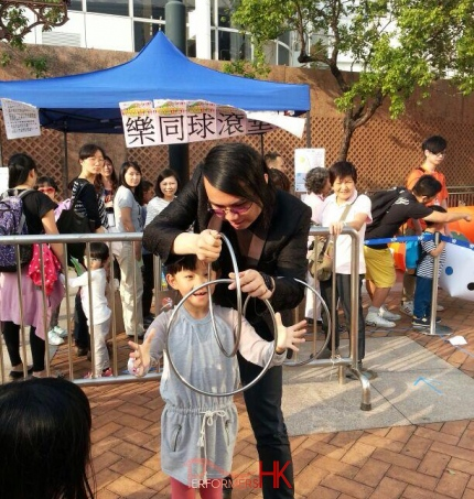 Magician performing three linking rings magic with a children audience at Hong Kong Kowloon Park