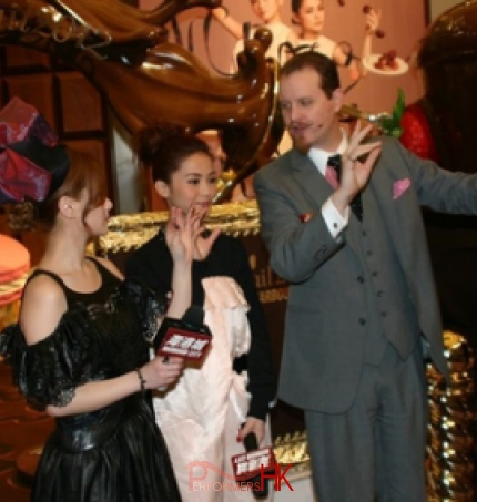 Magician performing stage magic vanishing and appearing wine bottle trick with Hong Kong celebrity at Chocolate Trail exhibition in Harbour City