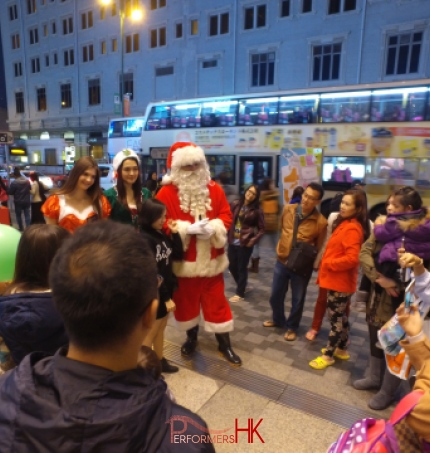 HK models and performer dress as Santa ,Santa girl and Elf standing outside Hong Kong greeting and photo taking with the guests at a Christmas corporate event.