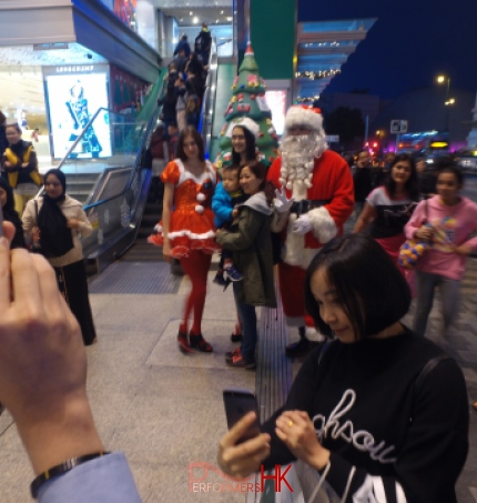 Hong Kong Xmas performers in Santa ,Santa girl and Elf costumes taking pictures with the guests at Sogo Christmas function.
