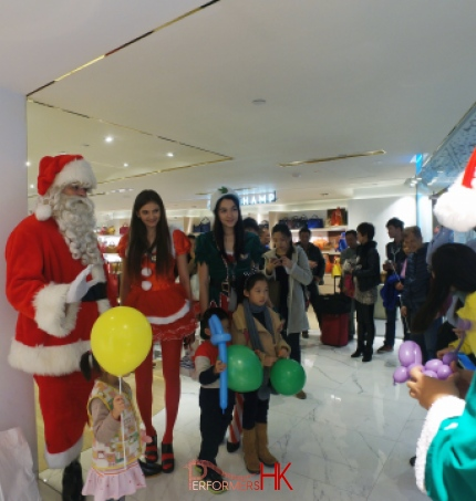 Santa performer with Santa girl and Elf models having a picture with three little kids who holding balloons at a Xmas event in Hong Kong