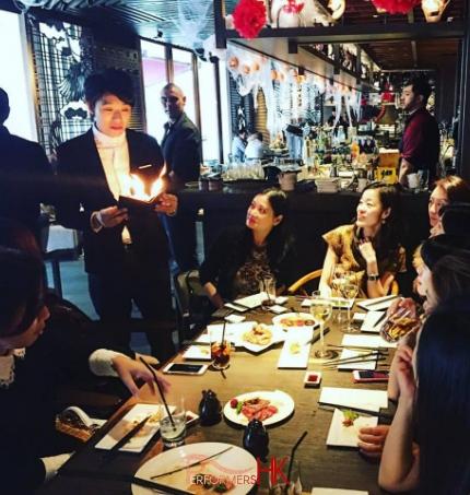 Magician performing roving fire magic to ladies at a Hong Kong restaurant