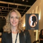 Business lady next to her portrait cutout at an exhibition