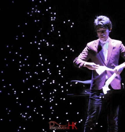 Magician in HK performing stage magic snow storm with white paper at corporate event.
