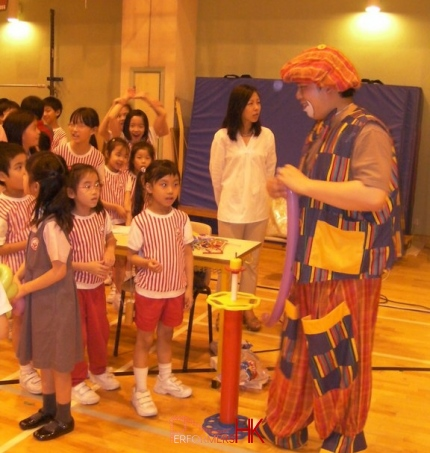 Student in Hong Kong all lined up to get a balloon from the balloon clown at a corporate school event