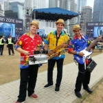 3 musicians in Hong Kong walk around performing at a summer event