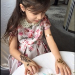 Little girl having three temporary henna tattoos on her both hands at a corporate party