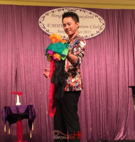 Magician in HK standing in the middle of magic hat and vase performing stage magic with colorful silks .