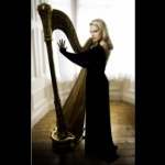 A HK harpist wearing a black dress posing next with the harp for a wedding