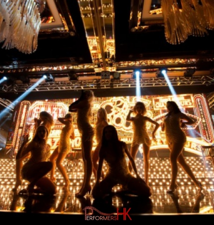 dancers on stage with gold background for crazy horse them event