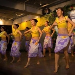 Seven female hula dancers doing hula chants and dancing for the audience.