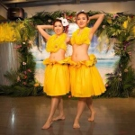 Two dancers dressed in yellow poses at the end of their performance.