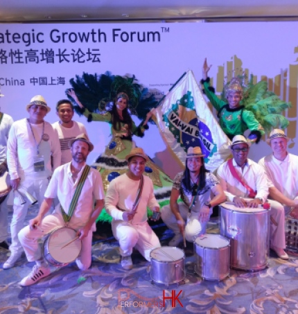 Percussion performers in white and dancers in green posing for photo