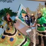Dancers and drummer in bright green and white costumes.