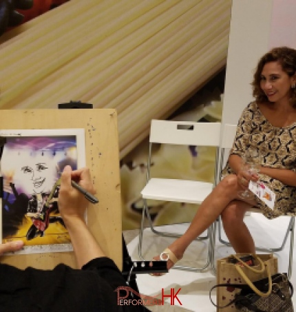 Lady getting her pic drawn by caricaturist