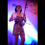 Erhu performer on stage at an event in China performing western music with traditional instruments