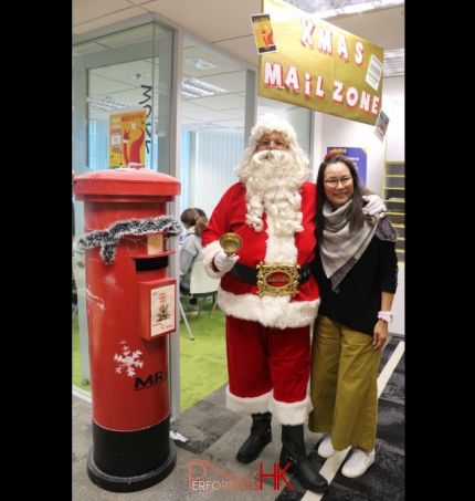 Santa standing next to a Xmas post box
