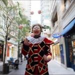 stilt walker juggling 5 balls whilst still walking in wan chai district hong kong