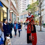 stilt walker interacting with passer by in lee tung avenue