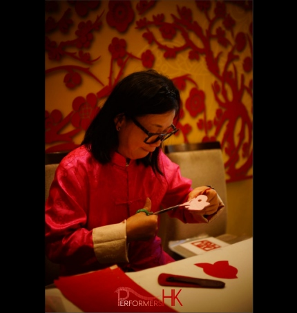 wearing pink traditonal chinese costume, artist is working on a cut out for guests