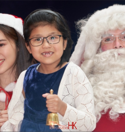 child holding bell in blue top with santa performer from performers hk