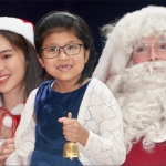 santa jay and santa girl with child holding bell