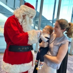 santa holding babys hand at hsbc office party