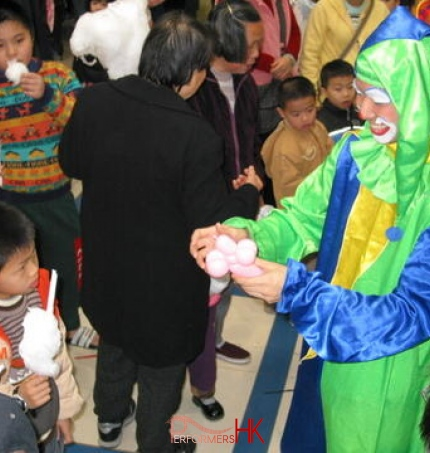 Hong Kong roving clown performer making a balloon for the little guest at a corporate family day event.