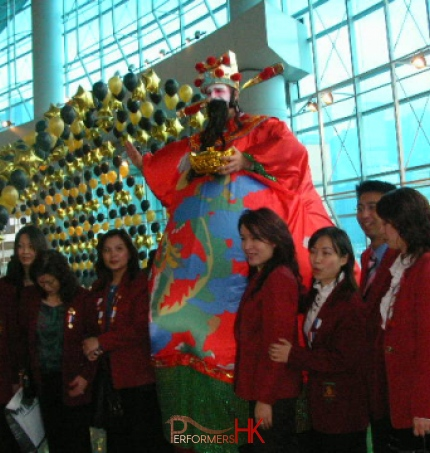 Stilt walker wearing giant inflatable Choi Sun costume at Hong Kong airport Chinese New Year event