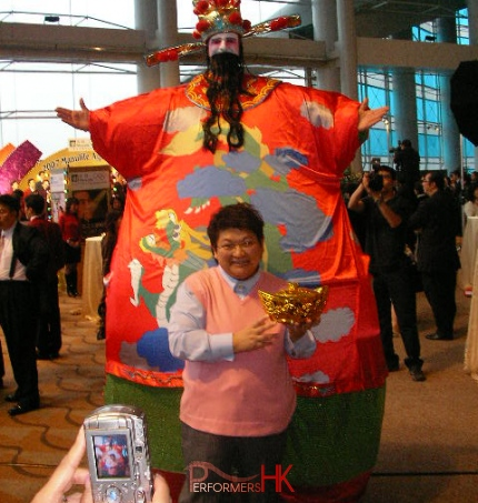 Giant Choi Sun performer in HK in inflatable costume taking picture with a gentlemen at corporate event
