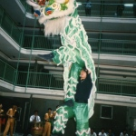 Two highly skilled lion dance dancers performing with their green lion.