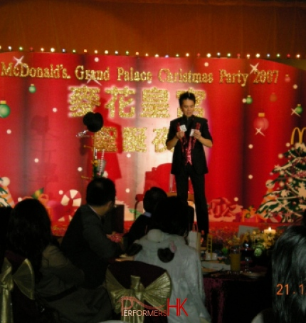 Magician standing next to the magic hat and Christmas tree performing stage card magic at Hong Kong McDonald corporate event.