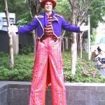 Hong Kong Stilt-walker wearing a purple and pink costume at a school event