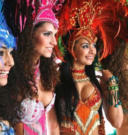 4 dancers in blue, pink, orange and green samba costumes